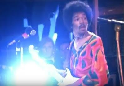 "Jimi Hendrix on stage at Isle of Wight. To the right of Jimi's Stratocaster headstock Hendrix road crew member Howard Parker, aka ""H,"" observes the troubled set."